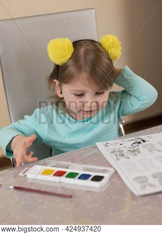 A Little Girl In A Cute Headband With Yellow Pompoms Draws With A Brush With Watercolor Paints