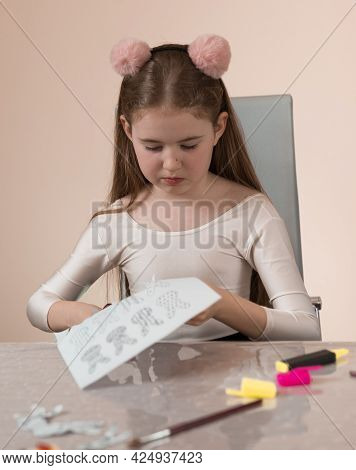 A School-age Girl Is Sitting At A Table And Is Concentrating On Cutting Jewelry And Gifts Out Of Pap