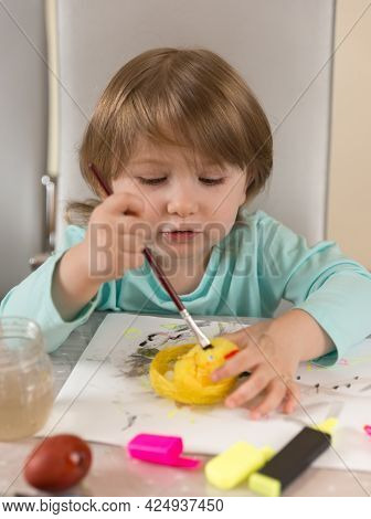 A Three-year-old Girl In A Turquoise Blouse Enthusiastically Paints A Yellow Chicken With Paints And