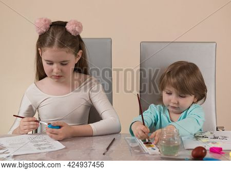 Two Sisters Of Different Ages Paint With Paints And Make Crafts-decorations For A Home Holiday