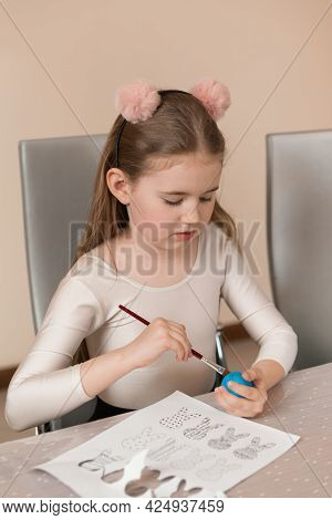 A Girl Draws A Pattern On A Colored Egg. Home Preparations For The Easter Holiday
