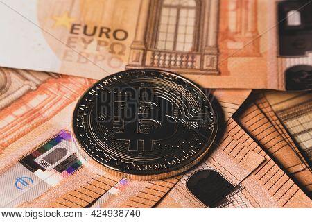Bitcoin Coin On Fifty Euro Banknotes Close-up.