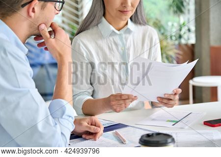 Senior Mature Asian Business Woman Boss Reading Report Of Young Intern Trainee In Modern Office. Tea
