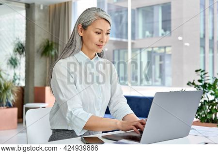 Successful Confident Asian Middle Aged Businesswoman Executive Top Manager Sitting At Desk Working T