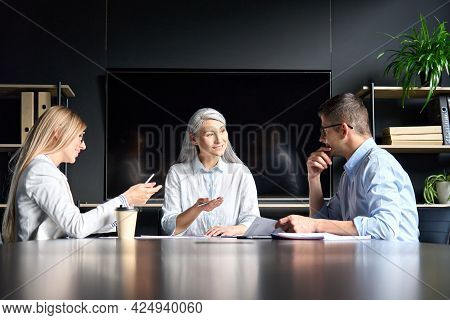 Senior Mid Aged Asian Executive Mentor Teacher Talking To Younger Male And Female Caucasian Colleagu