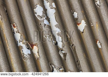 Photograph Of Brown Paint Peeling Off A Corrugated Iron Roof Due To Exposure To The Environment