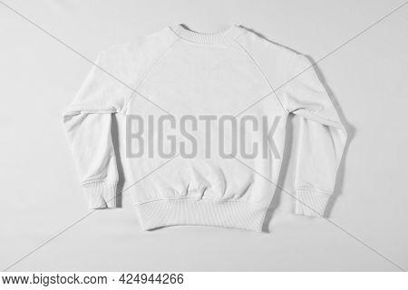 White Raglan Lying On A Light Background In The Studio. Sweatshirt For Brand Advertising Or Letterin