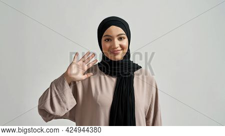 Happy Young Arabian Woman In Hijab Waving Hand While Looking At Camera On Light Background, Widescre