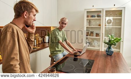 Same-sex Caucasian Male Couple Working On Laptop And Smartphone While Looking At Each Other In Moder
