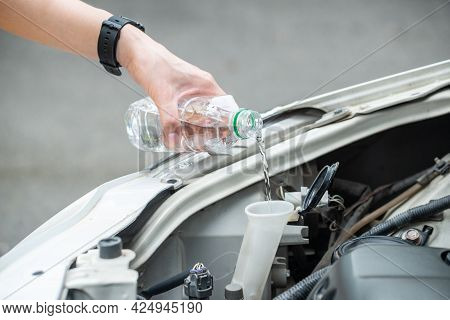 Cropped Shot Of Person Hand Filling Water Into Car Radiator For Reduce Engine Overheating. Engines C