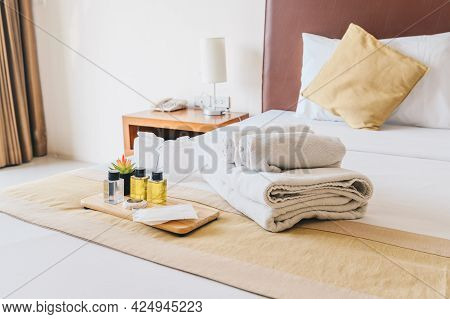 Group Set Of Free Hotel Amenities (such As Towels, Shampoo, Soap, Gel Etc) On The Bed. Hotel Ameniti