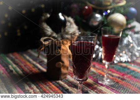 Red Wine In Crystal Glass With Bottle On Colorful Carpet With Creative New Year Artwork Decorations.