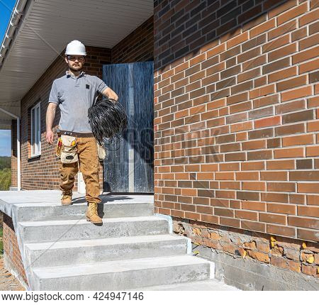 An Electrician Examines A Construction Site While Holding An Electrical Cable In His Hand At The Wor