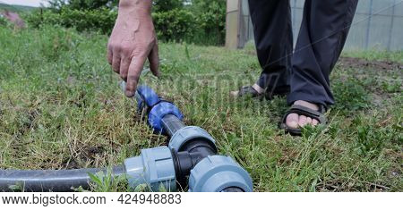 Checking The Irrigation System In A Private Household, A Partially Visible Man Checking The Plastic
