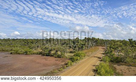 A Dirt Road Winding Through Bushland Beside Salt Pans Under A Cloudy Blue Sky In Australia