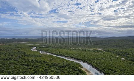 A Creek At Low Tide Winding Its Way Through Bushland Under A Cloudy Blue Sky At Cape Palmerston Aust
