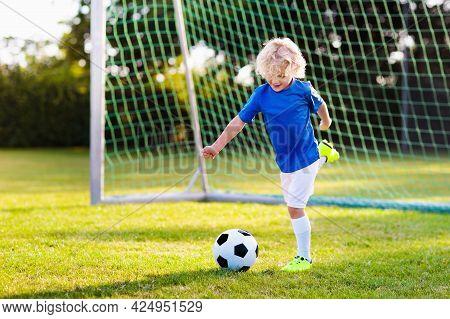 Kids Play Football On Outdoor Field. Children Score A Goal During Soccer Game. Little Boy Kicking Ba