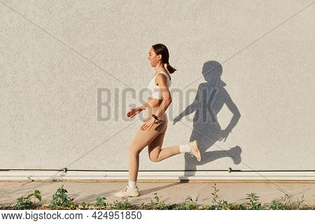 Side View Full Length Portrait Of Laughing Female Wearing White Top And Beige Leggins Running Outsid