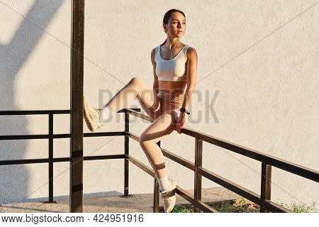 Outdoor Shot Of Woman Wearing White Top And Beige Leggins, Looking Away, Sitting On Stairs Railing,