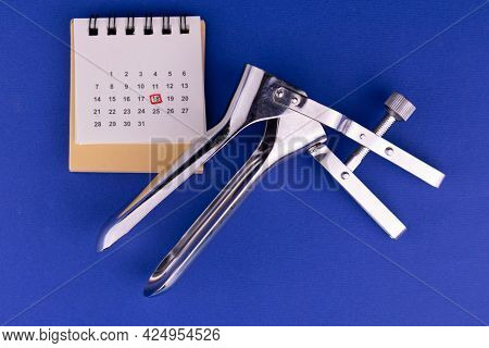 Gynecological Speculum And Date Stamped Calendar. Concept Of The Term At The Gynecologist.