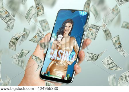 Beautiful Girl With Playing Cards In Her Hand On The Smartphone Screen And Falling Dollars. Online C