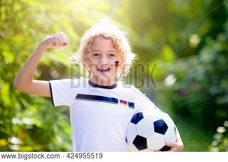 Kids Play Football On Outdoor Field. Germany Team Fans With National Flag. Children Score A Goal At