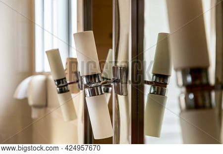 Closeup Of White Luminous Lamps Are Arranged In A Row Vertically On White Wall Near The Bathroom Lar