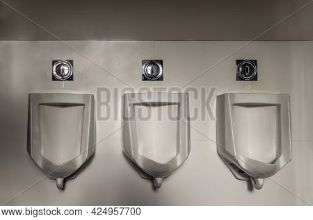 Closeup Of Three White Seperated Urinals And Automatic Infrared Flushing In Men's Bathroom, Design O