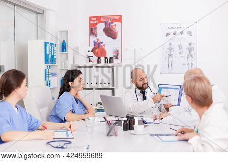 Physiotherapist Man Doctor Holding Clipboard In Hands Presenting Healthcare Expertise Explaining Sic