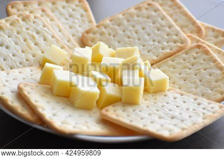 Crackers With Cheese In A White Plate On Wood Table.