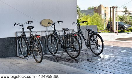 Bicycle Rental Service In The Hotel. Classic Black Bicycles Are Parked In The Metal Bike Parking In