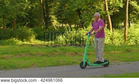 Handsome Senior Man Grandfather Tourist Riding Electric Scooter In Park. Modern Stylish Grandpa, New
