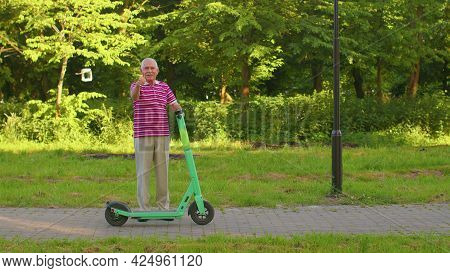 Senior Old Stylish Man Grandfather Riding Electric Scooter In Summer Park. Modern Grandpa Driving Ur