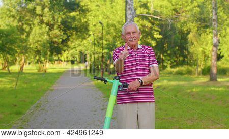 Caucasian Old Gray-haired Senior Man Grandfather Riding Electric Scooter In Summer Park. Active Mode