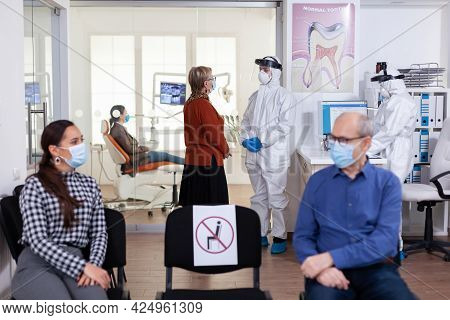Senior Woman Patient In Stomatology Clinic Discussing With Doctor Dressed In Ppe Suit As Safety Prec