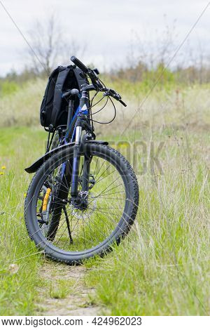 Mountain Bike, On The Field Road. Bike Stands On A Path In The Green Grass. Backpack On The Trunk. C