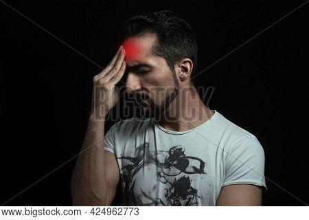 Headache. A Man Holding His Head From A Severe Headache On A Black Background.