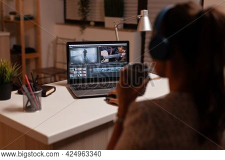 Filmmaker Editing Video Footage During Night Time In Home Kitchen. Content Creator In Home Working O