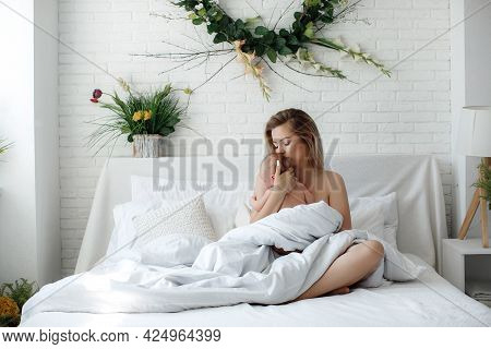 Beautiful Loving Young Mother And Small Baby Lying On Cozy Bed. Joyful Happy Caring Mom Hugs Cute Li