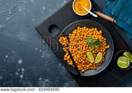 Fried Chickpeas With Turmeric With Parsley And Lime In Black Plate On An Old Black Table Background.