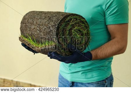 Young Man Holding Rolled Grass Sod At Backyard, Closeup