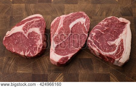 Close Up Three Raw Marbled Ribeye Beef Steaks Over End Grain Cutting Board Of Wooden Butcher Block,