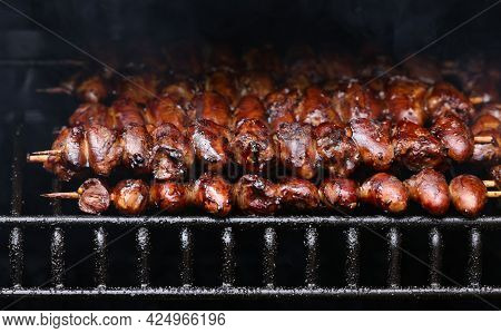 Close Up Searing And Smoking Glazed Chicken Yakitori Hearts On Wooden Skewers On Open Fire Outdoor G