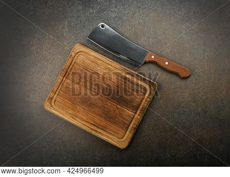Close Up One Butcher Metal Meat Cleaver And Oak Wood Chopping Board On Grunge Kitchen Table Surface,