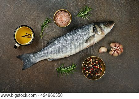 Close Up One Fresh Raw European Sea Bass Fish On Table, With Salt, Peppercorns, Rosemary, Garlic And