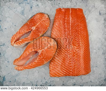 Close Up Fresh Raw Salmon Fish Fillet And Steaks On Background Of Crushed Ice On Retail Display, Ele