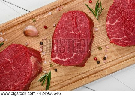 Close Up Three Aged Prime Marbled Raw Tenderloin Or Fillet Mignon Beef Steaks On Brown Oak Wood Cutt