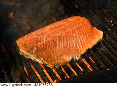 Close Up Searing And Smoking Salmon Fish Fillet On Open Fire Outdoor Grill With Cast Iron Metal Grat
