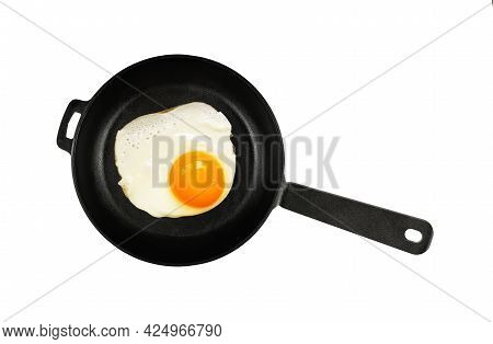 Close Up One Sunny Side Up Fried Egg On Black Cast Iron Frying Pan With Handle, Isolated On White Ba