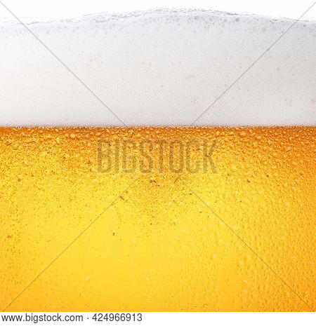 Close Up Background Texture Of Pouring Lager Beer With Bubbles And Froth In Frosty Glass With Drops,